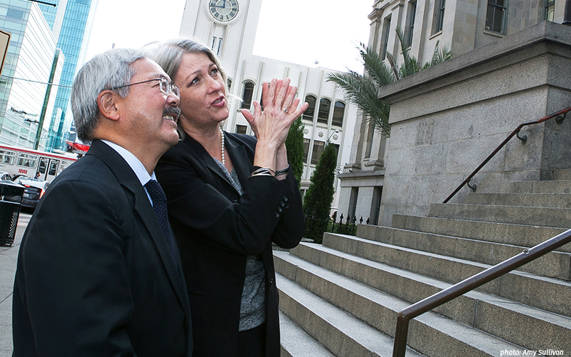 San Francisco Mayor Ed Lee looks on at the front of the Old U.S. Mint as Anthea Hartig, executive director California Historical Society (CHS) describes architectural details.  That California Historical, in partnership with the City and County of San Francisco, is receiving a $1 million grant from the State of California to explore, plan and conduct the required studies to help advance the next phase of development and implementation of the Old Mint Restoration Project.  (Photo credit: Amy Sullivan)